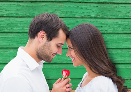 Digital composite of couple with flower with green wood background