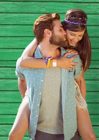 eyes are closed: Digital composite of happy hippy couple with green wood background