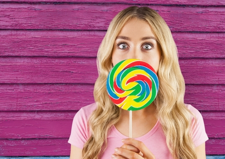 long hair model: Digital composite of hipster  with lollipop with pink wood background Stock Photo