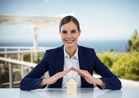 insurer: Digital composite of House under womans protective hands in resort