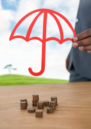 Digital composite of Cut out umbrella protective over money coins and landscape