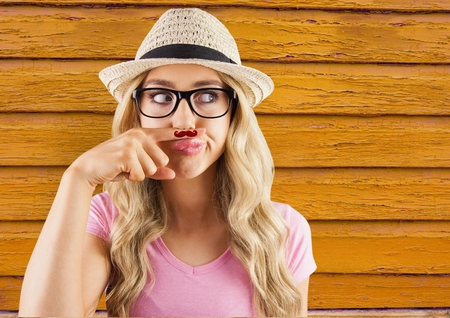 Digital composite of hipster woman with glasses with yellow  wood background
