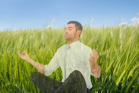 Digital composite of Man doing yoga in field of green sproutings