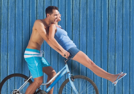 Digital composite of couple in bicycle with blue wood background Stock Photo