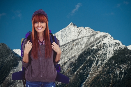 Digital composite of Red-hair woman smiling to the photo  in front of snow-covered mountains background Stock Photo