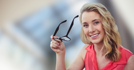 Digital composite of Happy blond-hair woman holding her glasses in hands