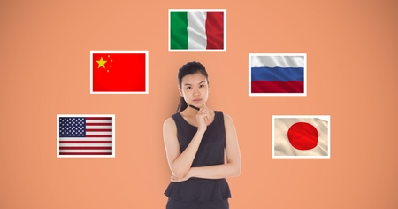 Digital composite of Portrait of beautiful woman holding pen standing by flags against orange background Stock Photo