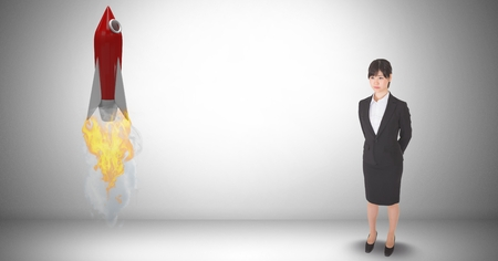 Digital composite of Digital composite image of businesswoman standing by rocket launch against gray background