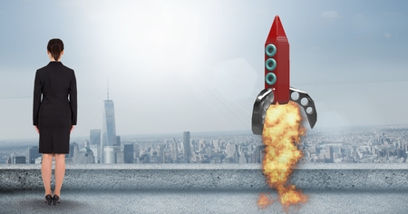 Digital composite of Rear view of businesswoman standing by rocket launch on terrace against city