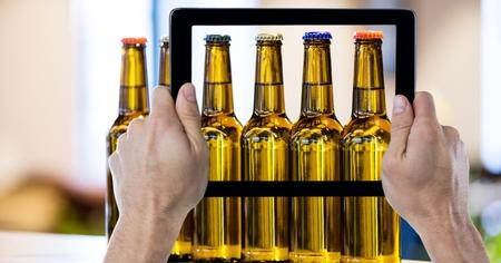 Digital composite of Hands photographing beer bottles through digital tablet at bar