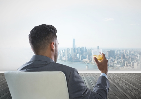 Digital composite of Rear view of businessman sitting on chair holding glass of alcohol while looking at city Stock Photo