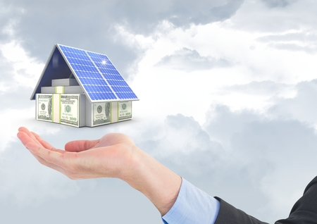 Digital composite of Digital composite image of currencies and solar panel above business hand against sky Stock Photo