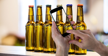 Digital composite of Hand taking picture of beer bottles through smart phone Stock Photo