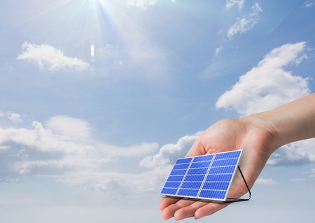 Digital composite of Digital image of solar panel on hand against sky during sunny day Stock Photo