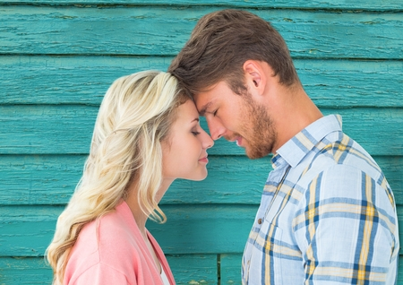 Digital composite of young happy couple with light blue wood background