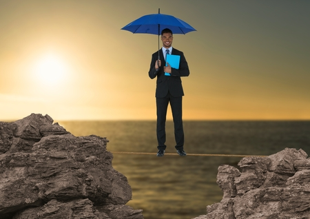 Digital composite of Digital composite image of businessman standing on rope holding diary with blue umbrella amidst rock