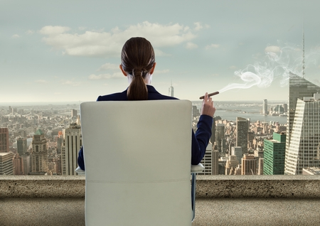 cigar smoking woman: Digital composite of Rear view of businesswoman sitting on chair and looking at city while smoking cigar Stock Photo