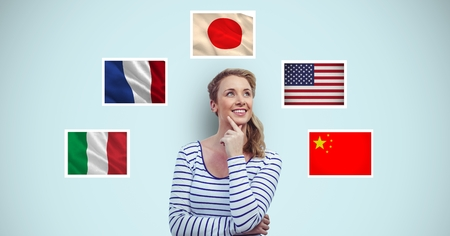 national women of color day: Digital composite of Thoughtful smiling woman standing by flags against blue background Stock Photo