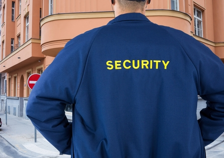 Digital composite of Rear view of security guard standing in city