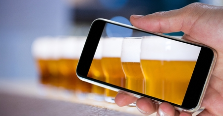 Digital composite of Hand photographing beer glasses through smart phone at bar Stock Photo