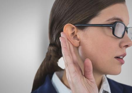 Digital composite of Businesswoman listening gossip against gray background Stock Photo