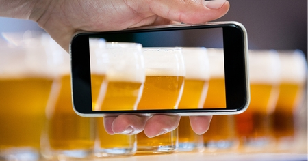 Digital composite of Hand taking picture of beer glasses through smart phone at bar