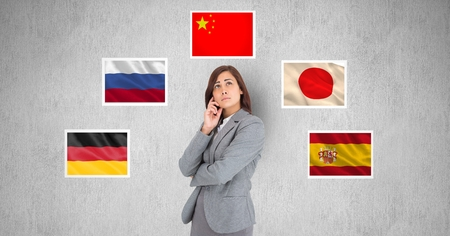 well dressed woman: Digital composite of Businesswoman thinking while standing by flags against gray background