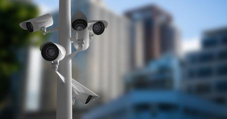 Digital composite of CCTV cameras against defocused buildings