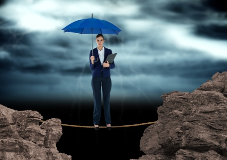 forked: Digital composite of Digital image of businesswoman standing on rope amidst rocks holding blue umbrella against cloudy sk