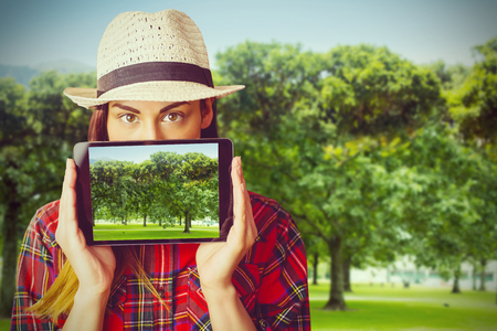 Portrait of woman hiding face with digital tablet  against park on sunny day