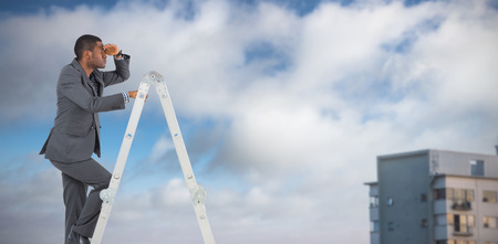 Businessman standing on ladder looking against cropped image of building against sky