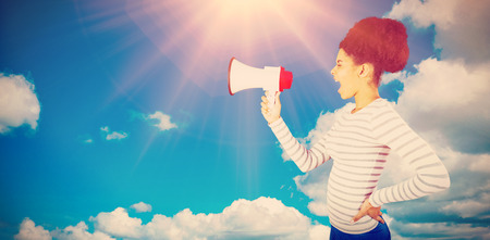 Carefree young woman shouting with megaphone  against scenic view of blue sky Stock Photo