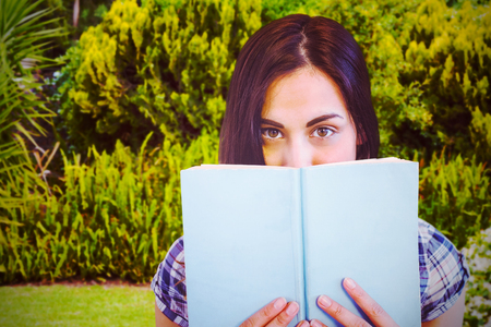 Close up portrait of woman hiding behind book against plants and trees growing