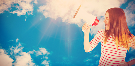Young woman yelling with megaphone  against view of beautiful sky and clouds Stock Photo