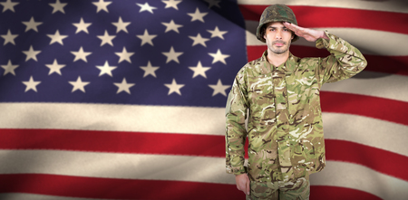 militant: Portrait of confident soldier saluting against close-up of american flag Stock Photo