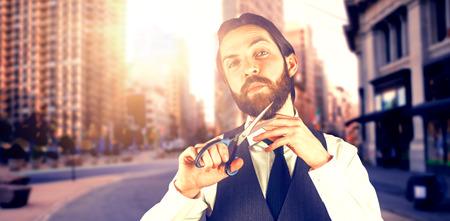 Portrait of businessman cutting beard through scissors against new york street