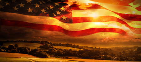 American flag waving on pole against country scene
