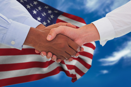 Close-up shot of a handshake in office against blue sky with clouds Stock Photo