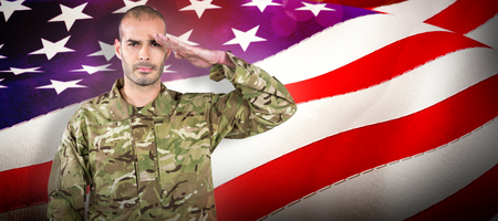 Portrait of confident soldier saluting against waving flag of america Stock Photo