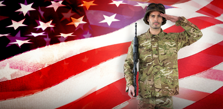 militant: Portrait of soldier with rifle saluting against waving flag of america Stock Photo