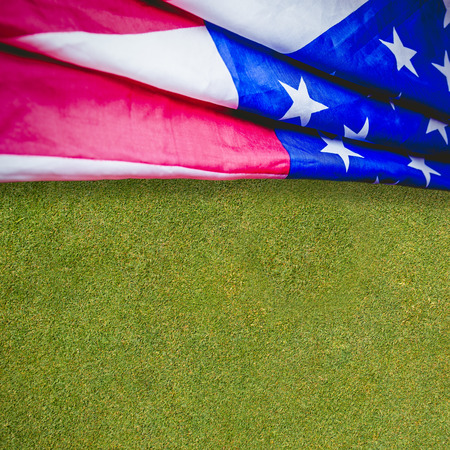 Creased US flag against closed up view of grass Stock Photo