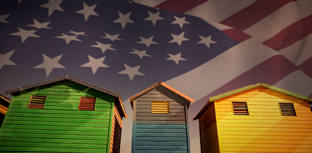 Close up of the us flag against low angle view of multi colored houses against sky Stock Photo