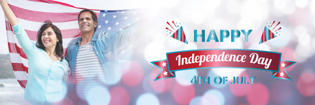 Digitally generated image of happy independence day message against mature couple holding american flag at beach