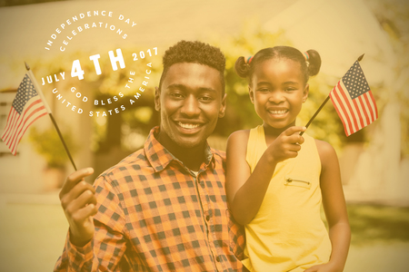 Multi colored happy 4th of july text against white background against happy father and daughter holding american flags on sunny day at park Stock Photo