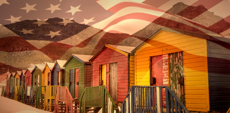 Focus on usa FLAG against multi colored wooden huts by mountain at beach Stock Photo