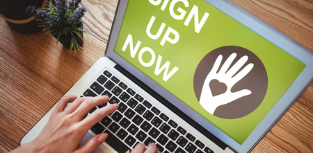 using tablet: Sign Up Now text with icons on green screen against hands of woman using laptop