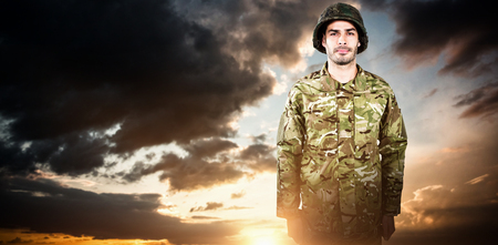 Portrait of confident military soldier standing against blue and orange sky with clouds