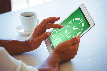 scrolling: Digitally generated image of Time To Give text with clock icon against man using digital tablet at cafe Stock Photo