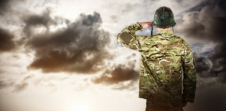 militant: Rear view of military soldier saluting against blue sky with white clouds