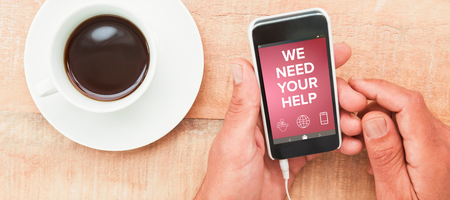 Digitally composite image of We Need your Help text with various icons  against hands holding smartphone next to cup of coffee Фото со стока